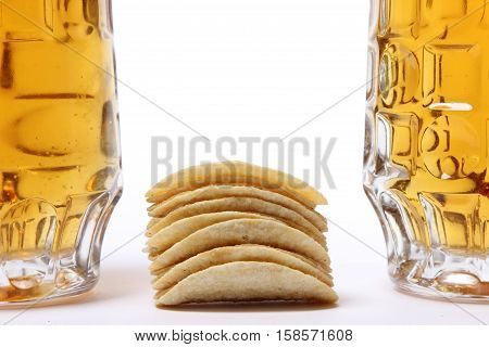 large mug of light beer. tasty beverage in a pint of beer on a white background. potato chips are stacked