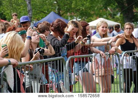 TENTERDEN, ENGLAND - JUNE 30, 2012: Music fans at the free Tentertainment music festival at Tenterden in Kent. Held in the public park the event is open to all and requires no credentials to attend.