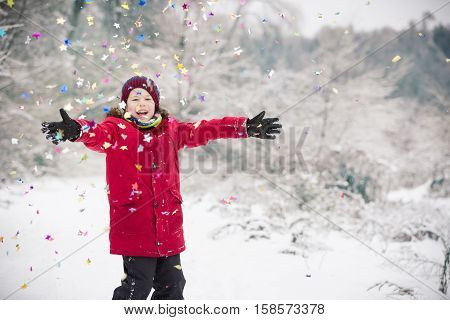 Happy kid boy with hands up with party confetti in winter park. Child having fun and Christmas celebration outdoors. Winter and holidays concept.