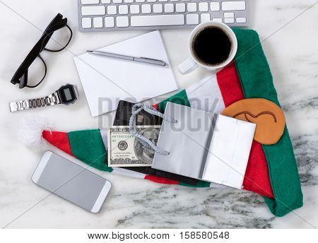 Overhead view of office desktop with computer keyboard cell phone shopping bag wallet money pen paper reading glasses coffee and Xmas Stocking on marble surface. Shopping for Xmas concept.
