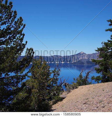 Wizard Island in the deep blue waters of Crater Lake as seen from the opposite bank on a sunny summer afternoon.