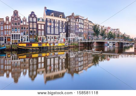 Amsterdam canal Singel with typical dutch houses, bridge and houseboats during morning blue hour, Holland, Netherlands.