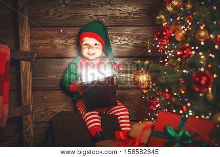 happy baby boy elf helper of Santa with a magic Christmas gift