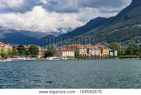 Lugano, Switzerland - August 25, 2013: Ships at the promenade of the luxurious resort in Lugano on Lake Lugano and Alps mountains in Ticino canton Switzerland.