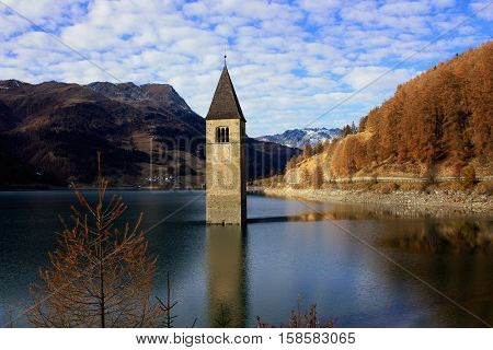 Beautiful landcape with th clock tower in Reschensee mountains Dolomits and blue sky with white clouds. Location Reschenpass on the border between the South Tyrol Italy and Austria.