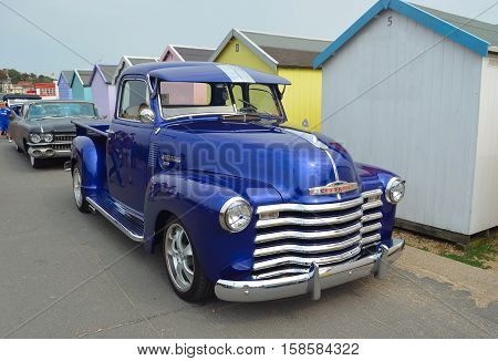FELIXSTOWE, SUFFOLK, ENGLAND - AUGUST 27, 2016: Classic Blue  Chevrolet 3100 pickup truck on seafront promenade in front of beach huts.