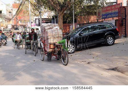 DELHI, INDIA - FEBRUARY 13 : Hard working indians pushing heavy load through streets of Delhi, India on February 13, 2016. Human labor is still cheaper than motorized vehicles.