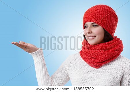 A beautiful woman with pleasant smile wearing warm winter clothes standing sideways raising her hand and looking aside. Young pretty woman wearing red scarf and hat on a blue background having holiday