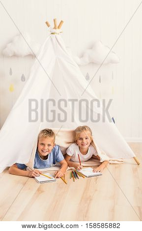 Best friends for lifetime. Little smiling children lying on floor in wigwam, covered with blanket and looking at camera