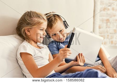 We love internet. Two happy kids looking at pad screen and using headphones while sitting on bed together