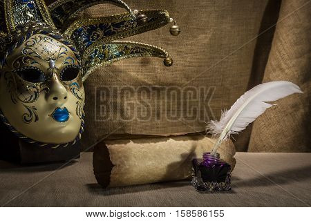 Literature concept. Old inkstand with feather near scroll and venezian mask on canvas background.