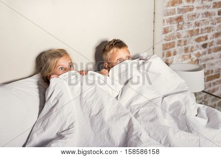 Horror movie. Scared little kids hiding behind white blanket while watching terrible story on tv