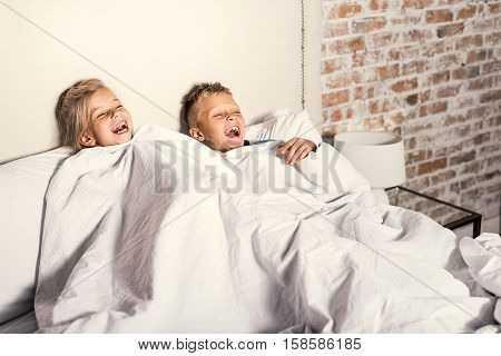 Today we viewing cartoons. Cute little brother and sister looking online funny program and laughing while lying under blanket