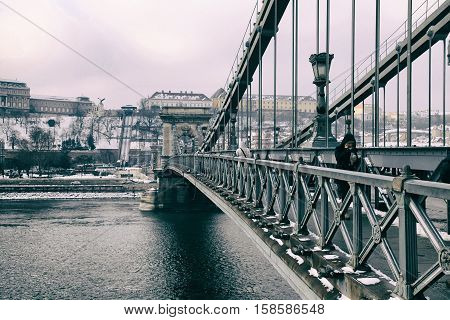 BUDAPEST, HUNGARY - JANUARY 5, 2016: People on The Szechenyi Chain Bridge in Budapest, Hungary. The Szechenyi Chain Bridge is a suspension bridge that spans the River Danube between Buda and Pest.