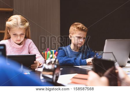 Concerned children are using their devices in classroom