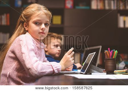 Calm teenager is sitting in dayroom and work with gadget