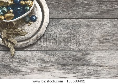 Over head flat lay view of rustic Christmas background. Grey wood. Vintage gold and blue ornaments on tarnished silver platter