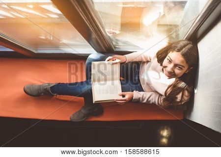 Fascinated girl is reading poetry volume and smiling happily. Top view