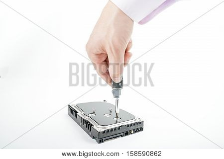 Hand repairman unscrews the 3.5 inch hard drive cover with a screwdriver. Isolated on white background.