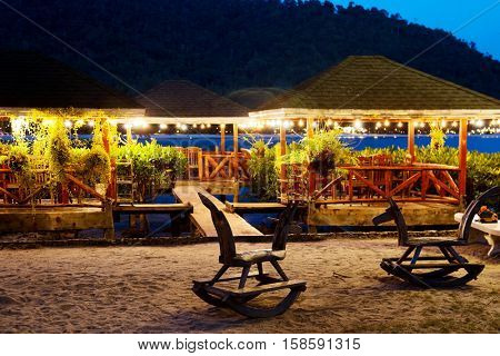 Wooden children's rocking chairs on the beach in the evening on a background lighted alcoves