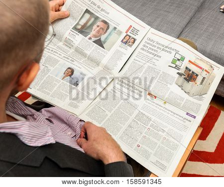 PARIS FRANCE - NOV 12 2016: Man reading Le Figaro French newspaper - about Unity Semiconductor business