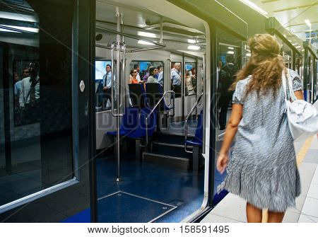 ISTANBUL TURKEY - JUL 28 2009: Rear view of woman in motion trying to catch the Istanbul metro train. It is the world's second-oldest underground urban rail line after the London Underground which was built in 1863