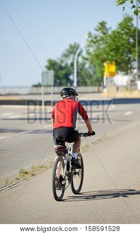 KEHL GERMANY - AUG 21 2015: Rear view of a senior cyclist riding a bike wearing specialised clothes and protection helmet - view from the rear