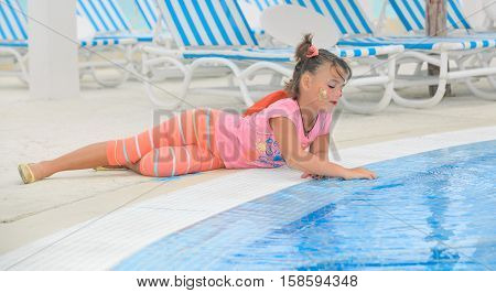 beautiful little girl laying down at the pool edge and softly touching the water