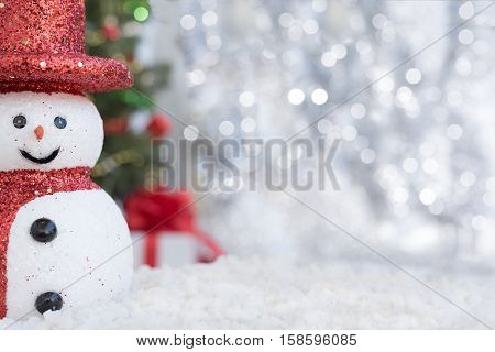 Christmas background with Snowman on snow over blurred christmas tree and gift box on glitter light bokeh backdrop with copy space