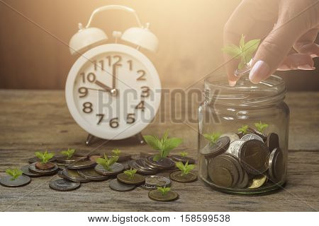 Women Hand Stacking Gold Coins With Wooden Background  And Clock .business Finance And Money Concept
