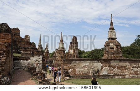AYUTTHAYA, THAILAND - November 4, 2016: People visiting the Wat Mhathat temple complex in Ayutthaya central Thailand