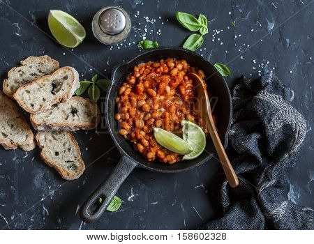 Braised beans in tomato sauce in a cast iron pan and homemade bread on wooden cutting board.