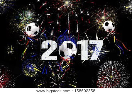 New Year 2017 celebration with soccer ball balloons and fireworks in night sky