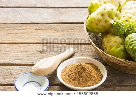 Noni fruit  and  noni powder on wooden table.Fruit for health and herb for health.