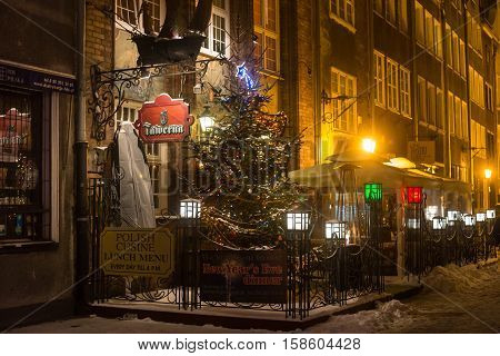 POLAND GDANSK - DECEMBER 30 2014: Night street of Gdansk in festive decoration before Christmas. Gdansk is a Polish city on the Baltic coast and popular center of tourism.