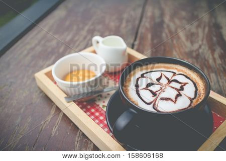 Hot coffee with foam milk art in afternoon break. Hot coffee with biscuit. coffee mocha on the wood desk.(selective focus vintage effect)