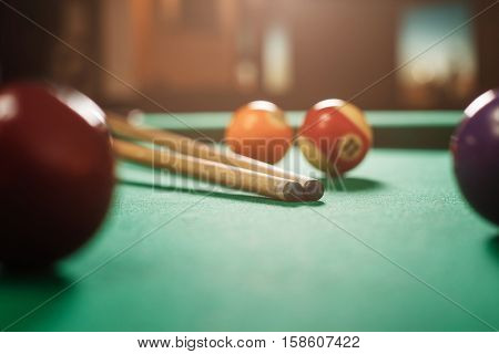 Two cues and spheres on a billiard table.