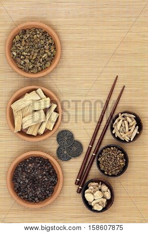 Traditional chinese herb ingredients used in alternative medicine, i ching coins and chopsticks over bamboo background.