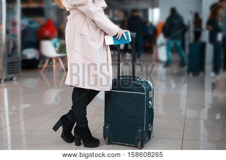 Legs of businesswoman with baggage in airport.