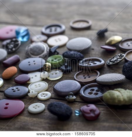 Lot of vintage buttons on old wooden table close up