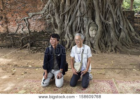 AYUTTHAYA, THAILAND - November 4, 2016: tourists being taken on picture on a respectful position in front of the sacred Head of the Buddha at Wat Mahathat Temple of the Great Relic a Buddhist temple in Ayutthaya central Thailand