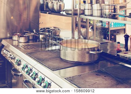 Professional kitchen interior, crock on stove, toned image