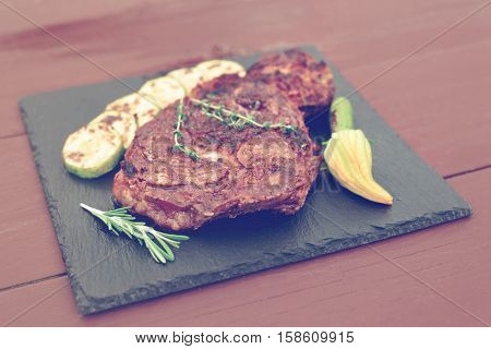 Rib eye steak with vegetables on a slate plate, toned image