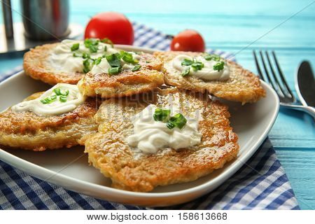 Plate with tasty potato pancakes for Hanukkah on wooden table, closeup