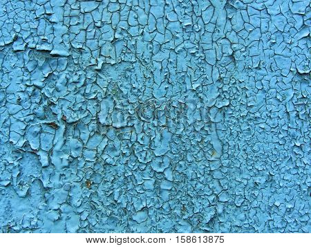 Old cracked paint pattern on wall. Peeling paint. Pattern of rustic blue grunge material. Damaged paint. Wall covered with cracked paint. Flaking paint on a concrete wall. Scratched old surface.
