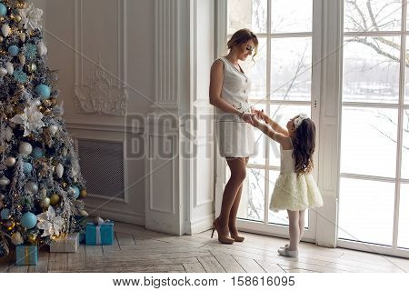 mother and daughter three years standing by the large window in white dresses before the new year