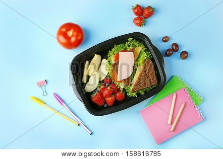 Lunchbox with tasty dinner and stationery on blue background