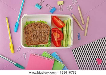 Lunchbox with dinner and stationery on pink background