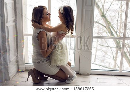 mother and daughter three years sitting by the large window in white dresses before the new year
