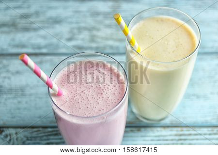 Delicious fruit milkshakes on wooden background